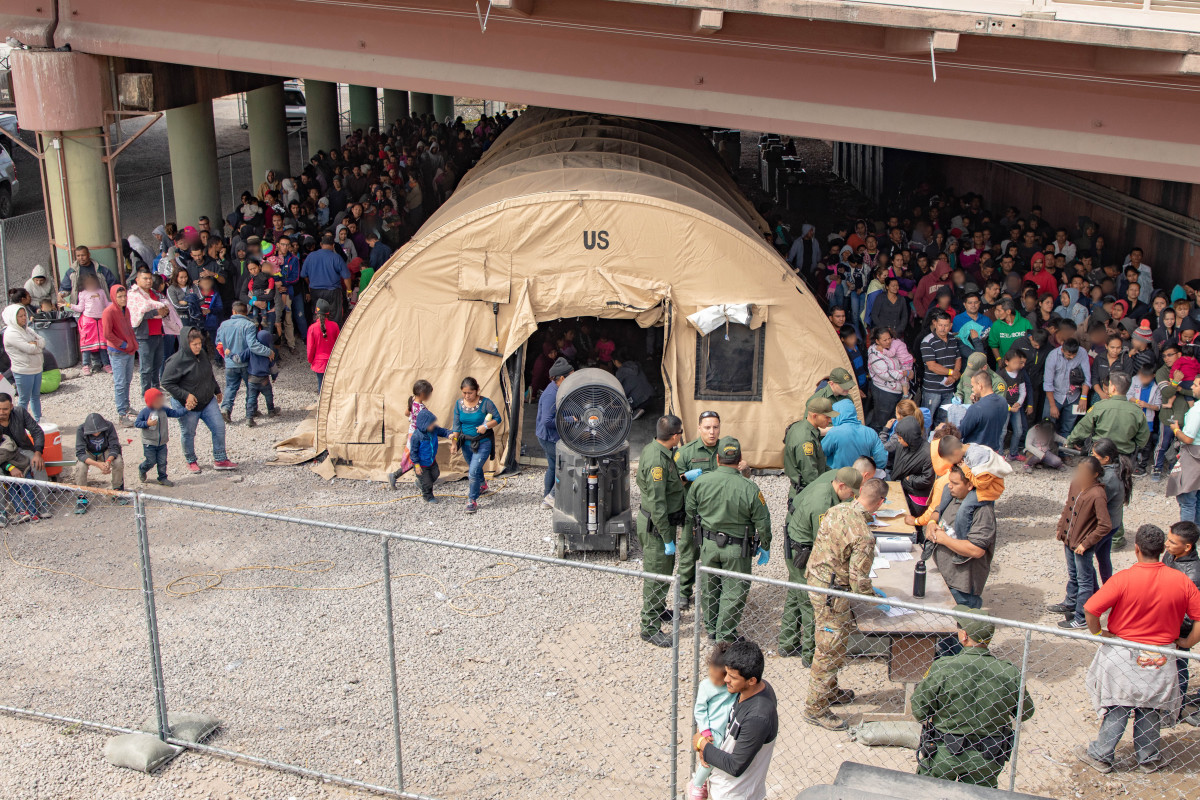 U.S. Border Patrol agents provide food, water, and medical screenings to scores of migrants and asylum seekers held underneath the international pedestrian bridge between the United States and Mexico on March 22nd in El Paso, Texas.