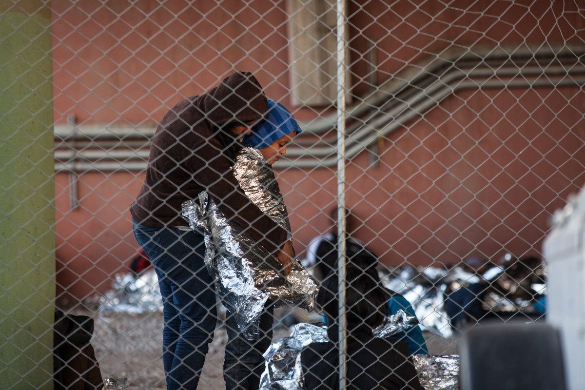 Children and families huddle against the cold wind. CBP provided mylar blankets.
