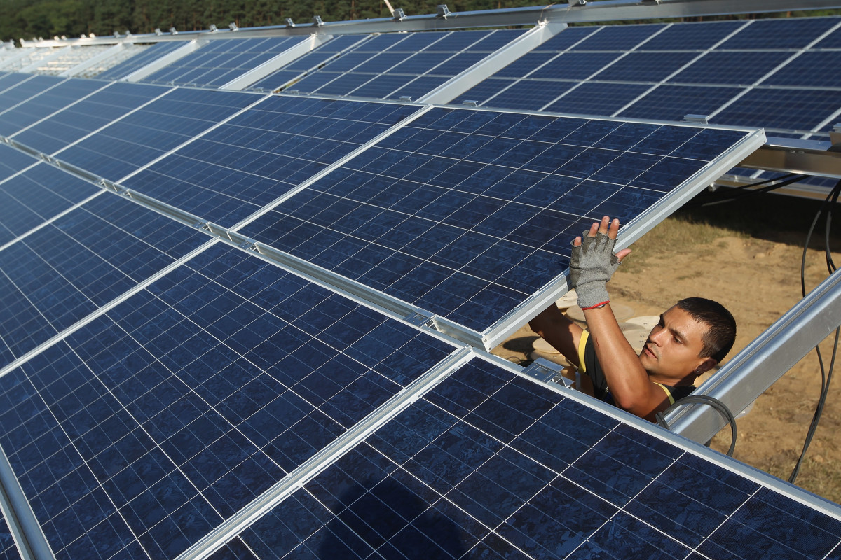 A worker installs solar panels containing photovoltaic cells.