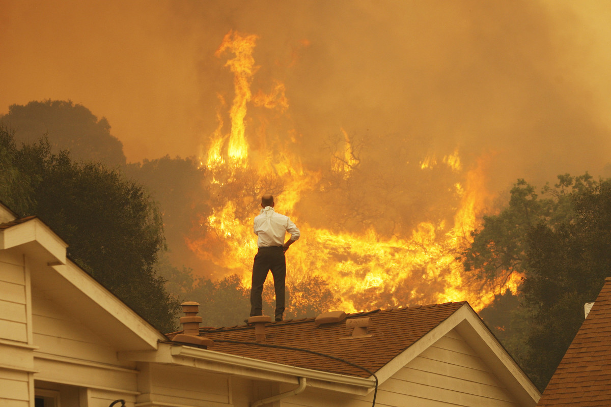 A man on a rooftop looks at approaching flames as the Springs fire continues to grow on May 3rd, 2013, near Camarillo, California.
