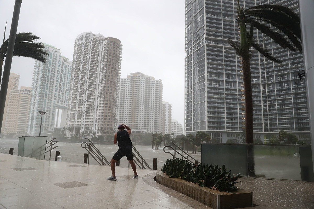 A person battles high winds and rain to take pictures of the flooding along the Miami River as Hurricane Irma passes through on September 10th, 2017, in Miami, Florida.