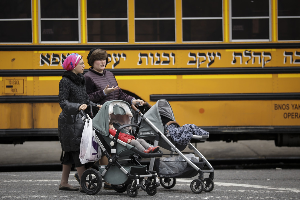 Women pushing strollers walk past the Yeshiva Kehilath Yakov School in the South Williamsburg neighborhood, on April 9th, 2019, in the Brooklyn borough of New York City.