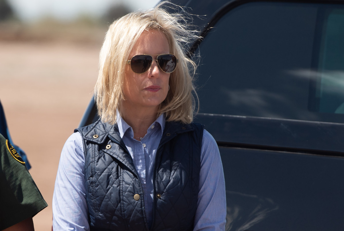 In this photo taken on April 5th, 2019, Secretary of Homeland Security Kirstjen Nielsen waits for President Donald Trump as he arrives to tour the border wall between the United States and Mexico in Calexico, California.