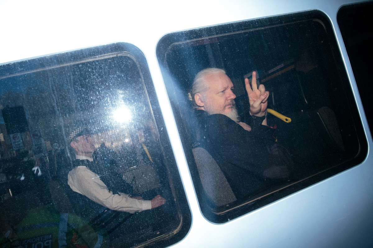 Julian Assange waves to the media from a police vehicle on his arrival at Westminster Magistrates' Court on April 11th, 2019, in London, England.
