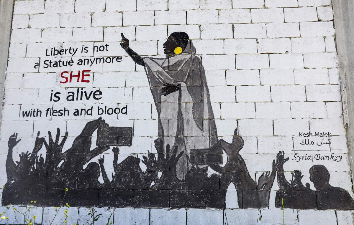 "This picture taken on April 12th, 2019, shows a view of a mural painting of Alaa Salah, a Sudanese woman propelled to Internet fame after clips went viral of her leading powerful protest chants against President Omar al-Bashir, painted by the Syrian artists collective Kesh Malek (Checkmate) on the wall of a farmhouse building in the rebel-held Syrian town of Kafranbel in the northwestern Idlib province. Dubbed online as ""Kandaka,"" or Nubian queen, Salah has become a symbol of the protests, which she says have traditionally had a female backbone in Sudan."