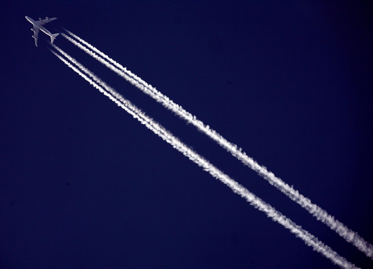 A commercial airliner flies across the sky.