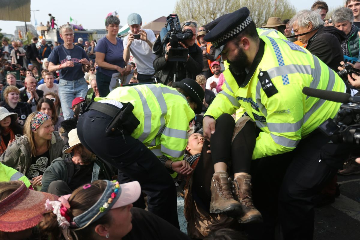 A climate change activist is pulled out of the crowd to be arrested by police officers at Waterloo Bridge in London on April 18th, 2019, during an environmental protest by the Extinction Rebellion group.