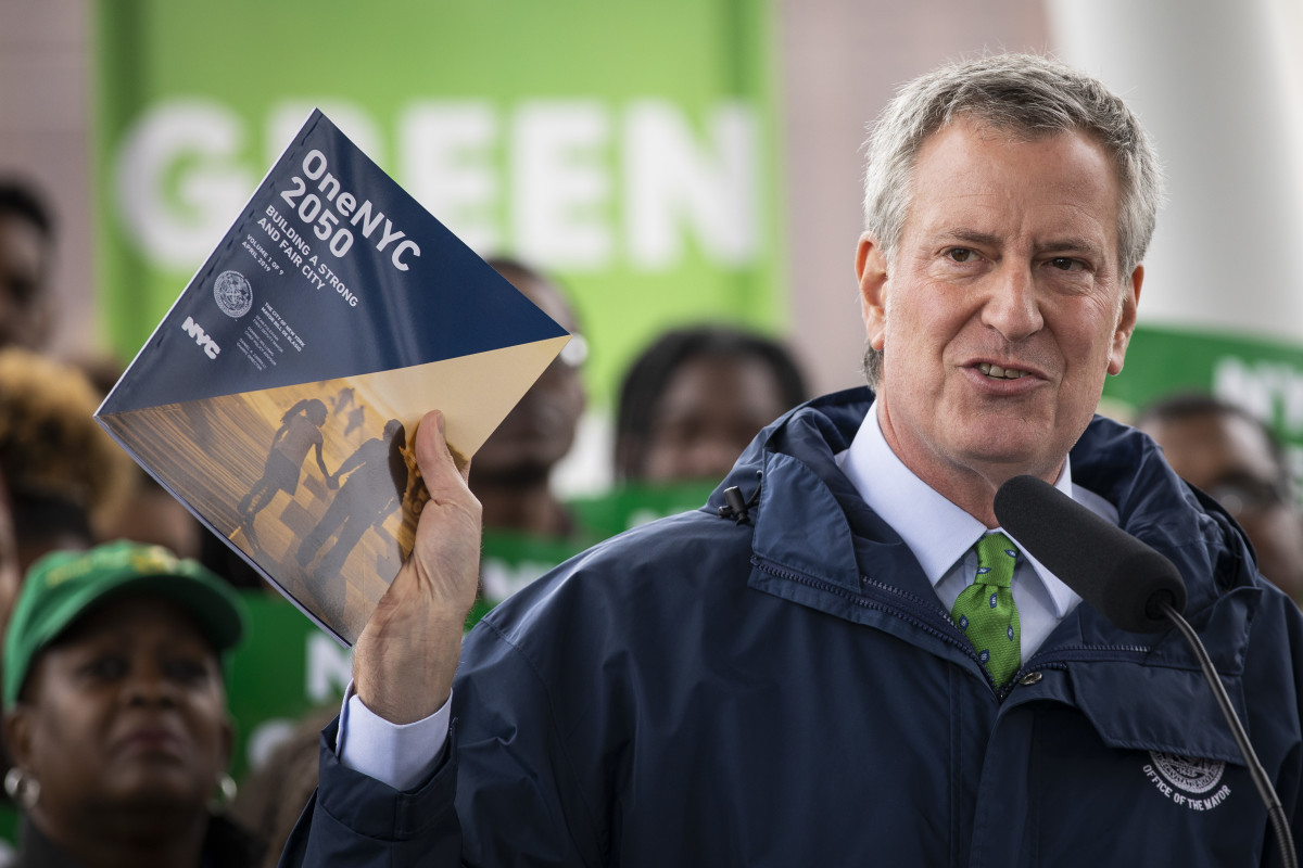 New York City Mayor Bill de Blasio holds up a copy of the One NYC 2050 plan as he speaks about the city's response to climate change at Hunter's Point South Park on April 22nd, 2019, in the Queens borough of New York City. The Climate Mobilization Act, which has been referred to as a Green New Deal for the city, passed the city council last Thursday. The legislation, which is part of a broader plan to reduce the city's carbon footprint, would require private building owners to cut their emissions by 40 percent by 2030. The One NYC 2050 report, released Monday, includes plans for how the city can meet that goal.