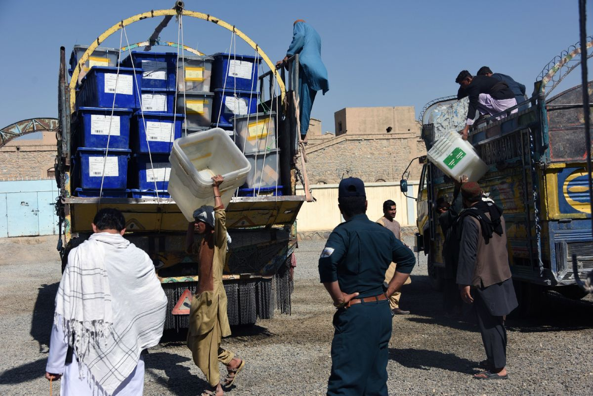 Afghan employees of the Independent Election Commission unload ballot boxes from a truck at a polling center ahead of legislative election in Kandahar Province on October 26th, 2018.