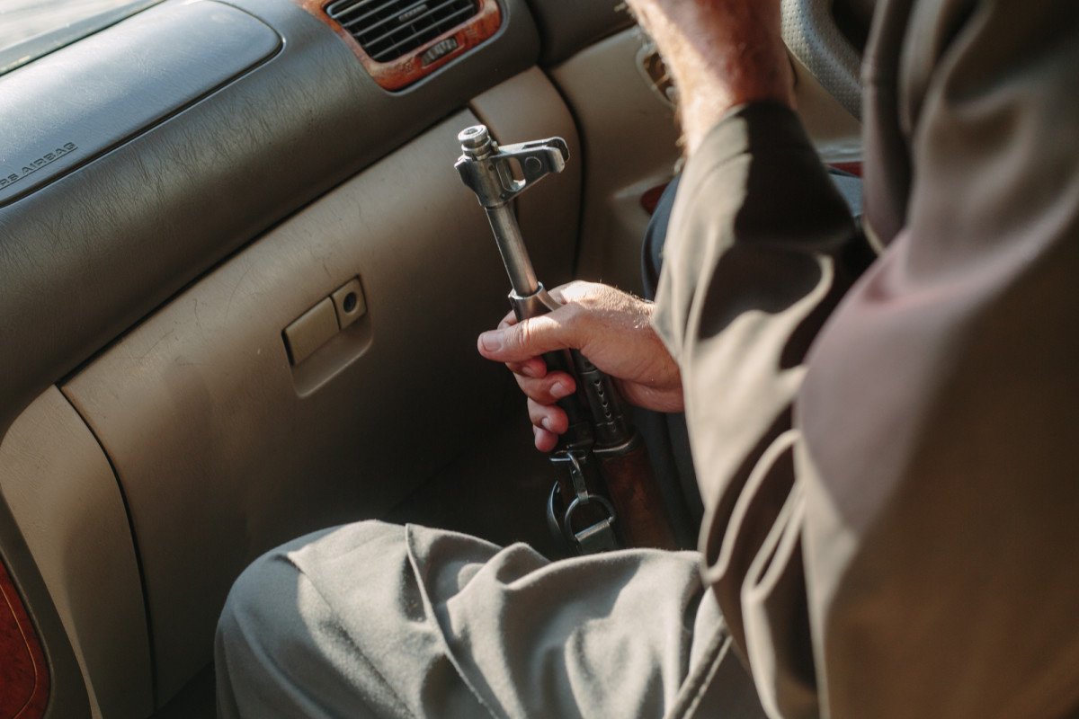 A member of Nasib's campaign team clutches an AK-47 while the team drives through Kabul, days before the parliamentary election.