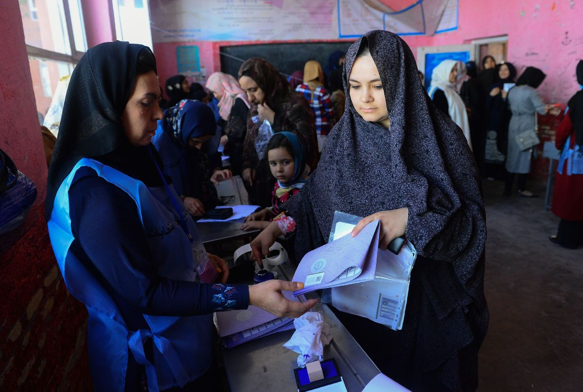 An Afghan Independent Election Commission official (L) prepares ballot papers for voters at a polling center for the country's legislative election in Herat Province on October 20th, 2018.