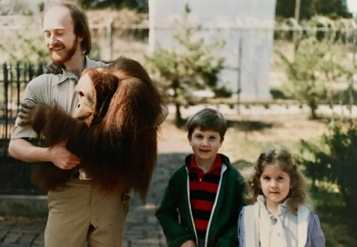 Zookeeper Dick Haskin poses for a photo with Chewy, a sumatran orangutan, and two young visitors at the Lincoln Children's Zoo.