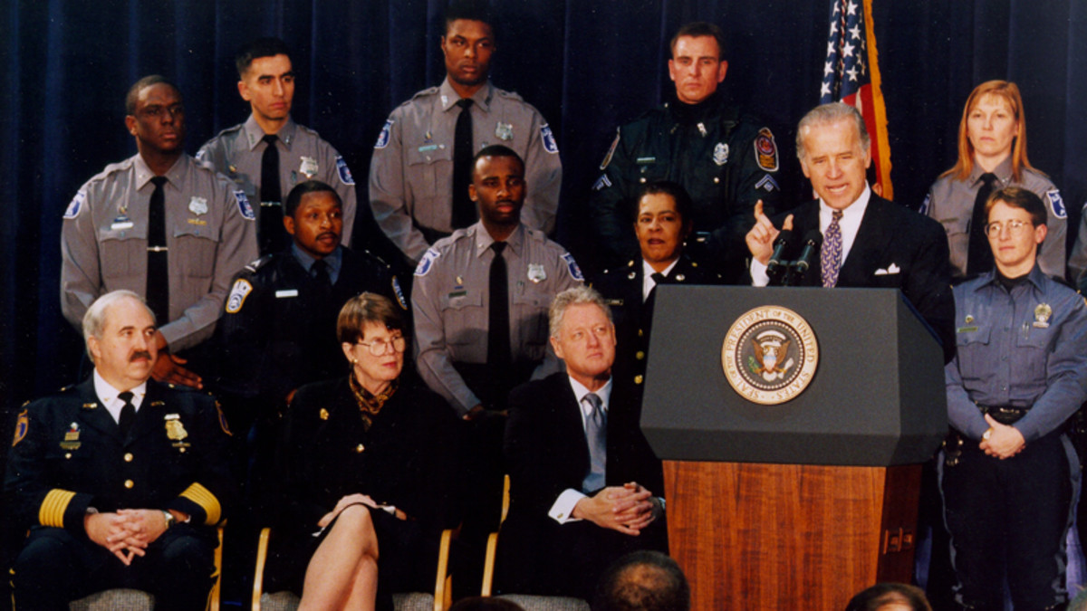 Then-Senator Joe Biden speaks at the signing of the Violent Crime Control and Law Enforcement Act of 1994, as Attorney General Janet Reno, President Bill Clinton, and local law enforcement officials look on.