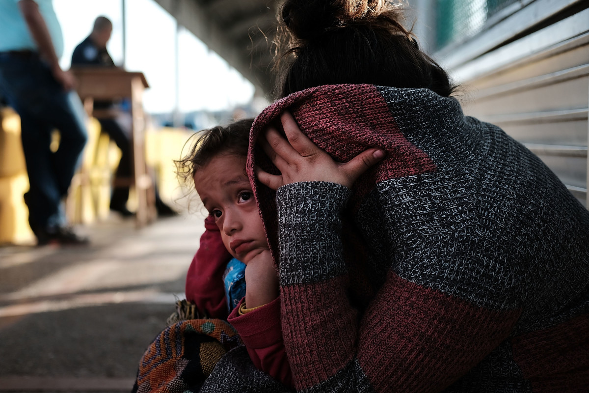 A Honduran child and her mother, fleeing poverty and violence in their home country, wait along the border bridge after being denied entry from Mexico into the U.S.