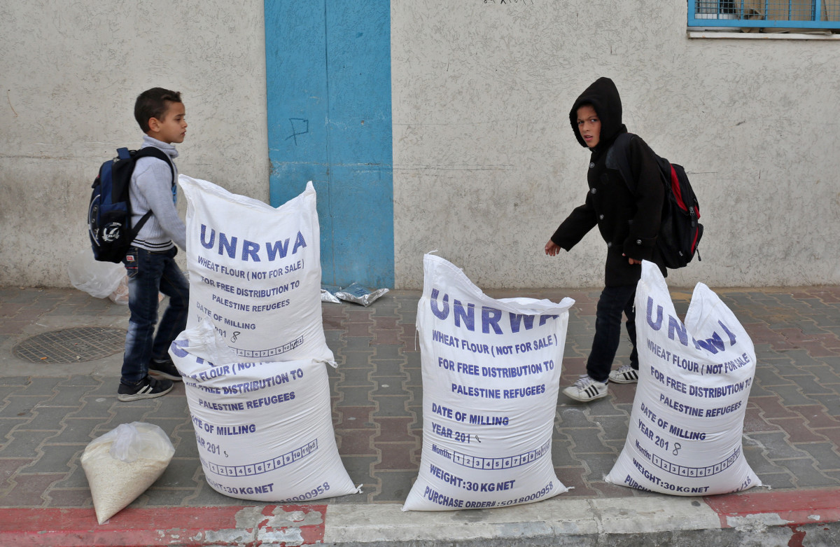 Palestinian schoolboys walk past sacks of flour outside an aid distribution center run by the United Nations Relief and Works Agency, in Rafah in the southern Gaza Strip, in December of 2018.