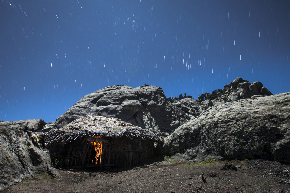 A cook fire glows inside a hut on the Ethiopian Highlands.
