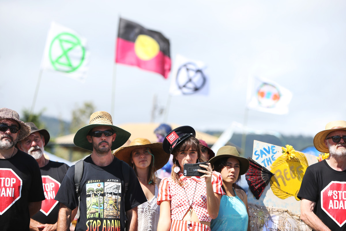 Environment activists and members of the public stand at the edge of Airlie Bay during an anti-Adani Carmichael coal mine rally on April 26th, 2019, in Airlie Beach, Australia.