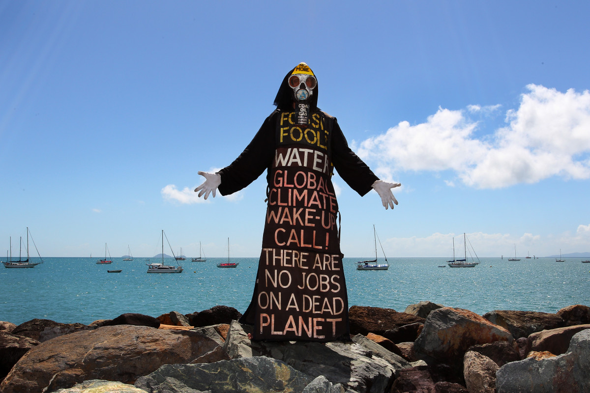 Benny Zable, a performance artist for peace and environment, stands in costume at the edge of Airlie Bay during an anti-Adani Carmichael coal mine rally on April 26th, 2019, in Airlie Beach, Australia.