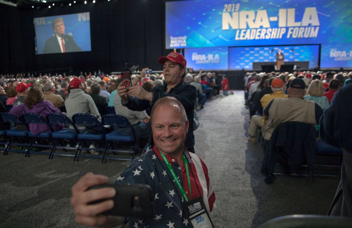 Skippy Thomas, a member of the National Rifle Association, takes a selfie with President Donald Trump in the background during the NRA's annual meeting at Lucas Oil Stadium in Indianapolis, Indiana, on April 26th, 2019.