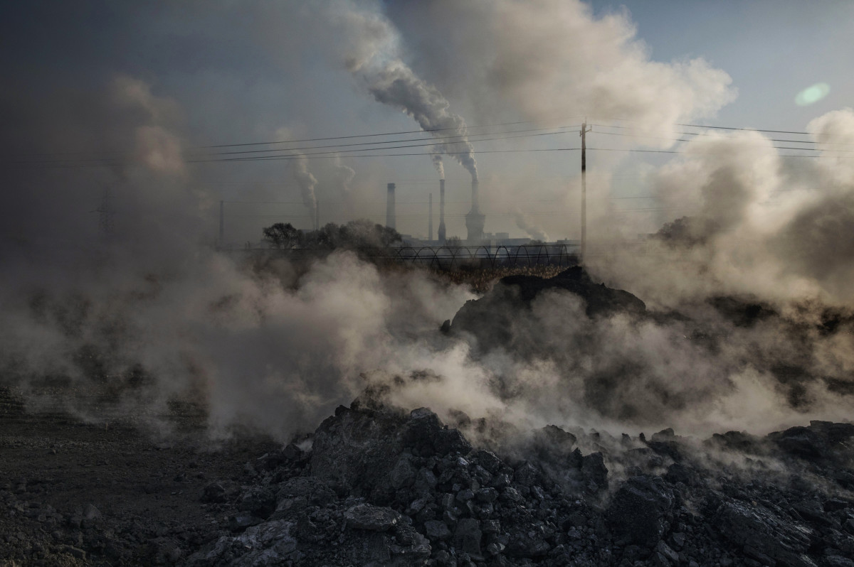 Steam and smoke from waste coal and stone rises after being dumped next to an unauthorized steel factory.