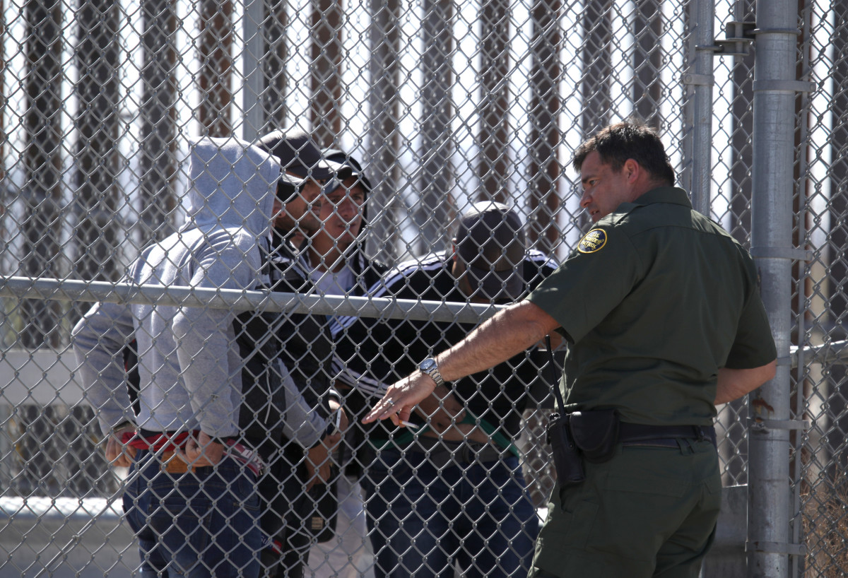 A U.S. Border Patrol agent talks with detained migrants at the border of the United States and Mexico on March 31st, 2019, in El Paso, Texas.