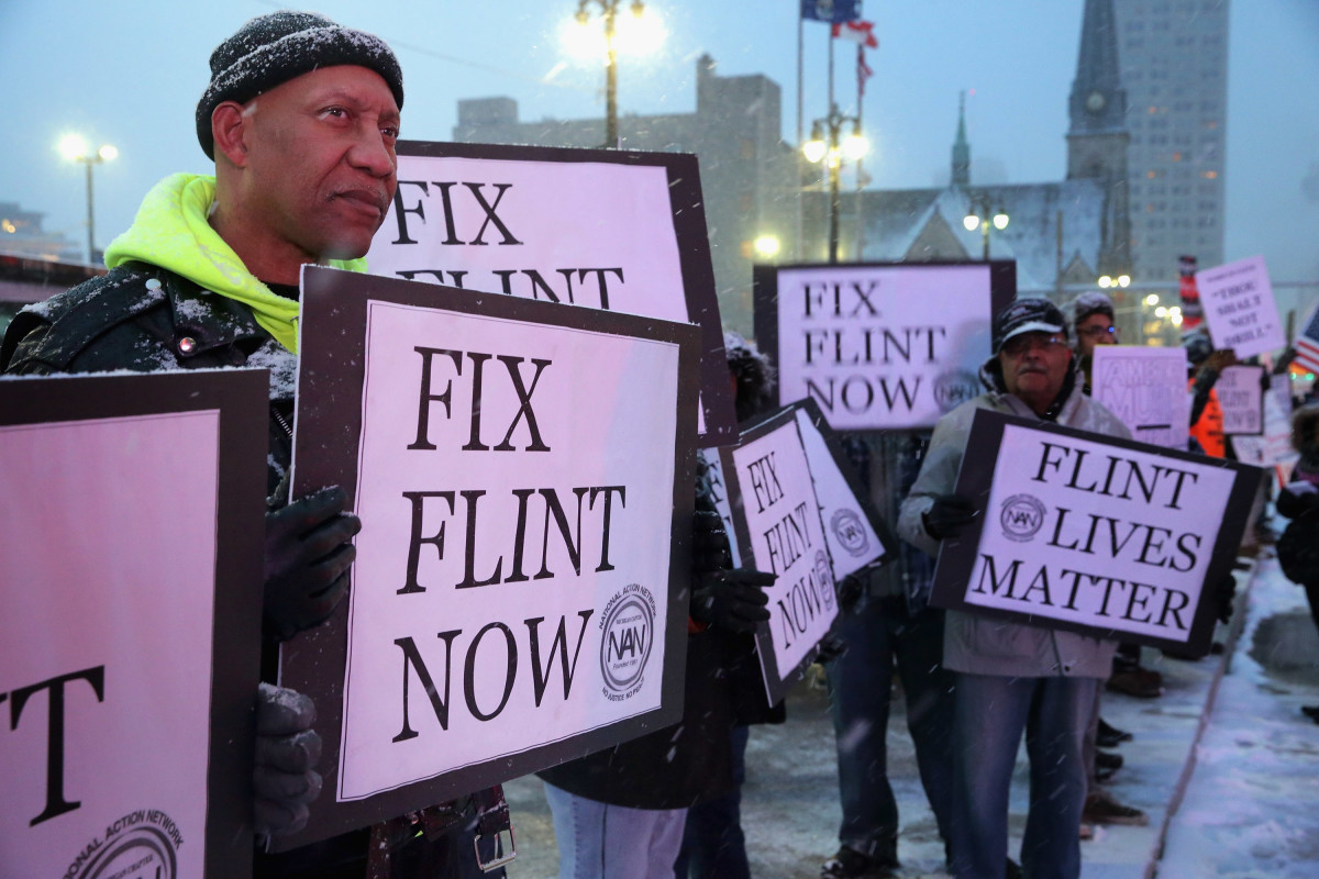 Demonstrators demand action from the Republican presidential candidates about the water crisis in Flint outside the historic Fox Theater.