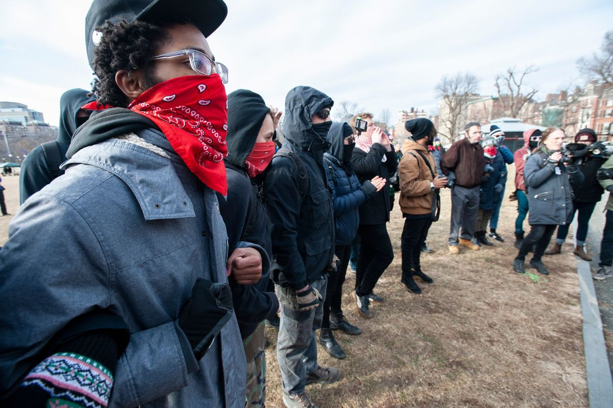 Anti-fascist counter-protesters form a circle around the helmeted members of a right-wing group during the Women's March at Boston Common in Boston, Massachusetts, on January 19th, 2019.