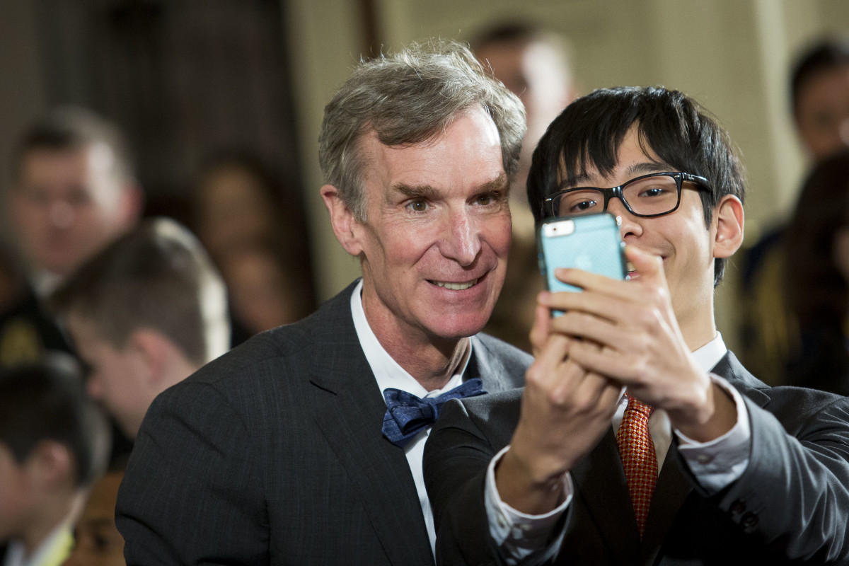 Scientist Bill Nye takes a selfie photo with a student.