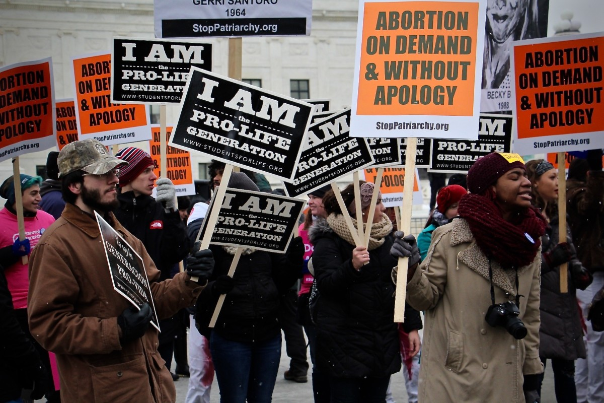 People carry pro-life and pro-choice signs during the 2016 March for Life in Washington, D.C.